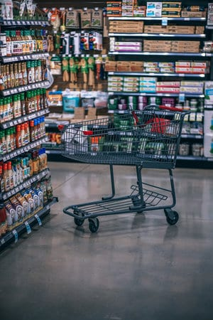 empty grocery cart in grocery store aisle