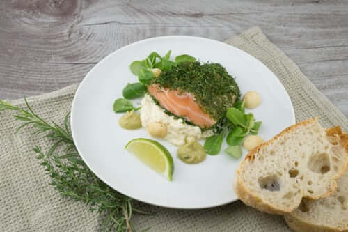 salmon on a plate with green garnish