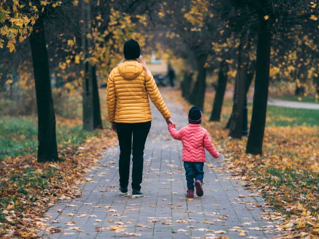 woman in yellow jacket walking with small child in pink jacket in fall weather