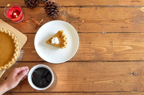 relaxing with a cup of coffee paired with pumpkin pie promoting holiday wellness.