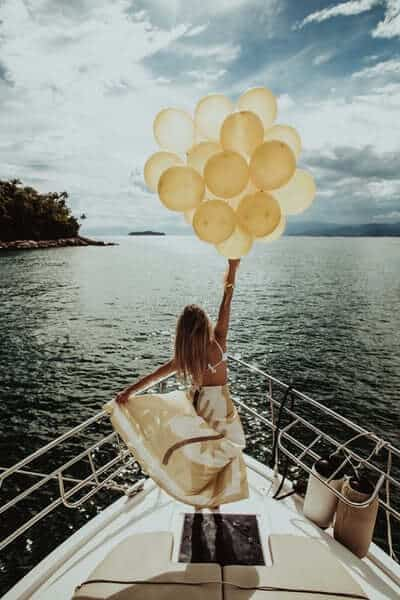 Woman on boat with yellow balloons