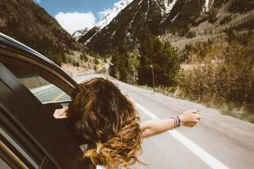 Woman with head out window of car on highway
