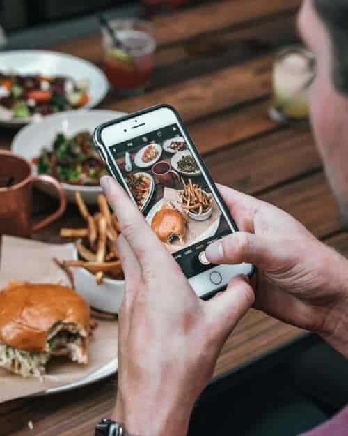 person holding phone taking photo of food