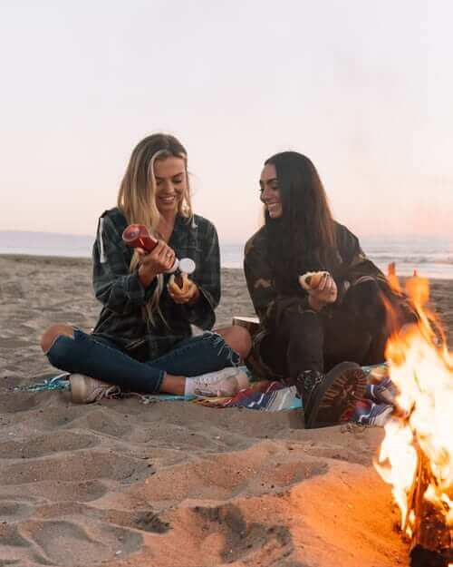 Two girls next to.a fire eating