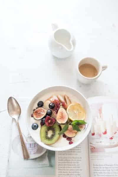 Bowl of fruit and cup of coffee with spoon on the left side