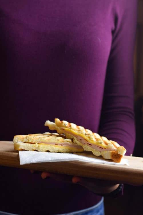 Woman in purple shirt holding a sandwich