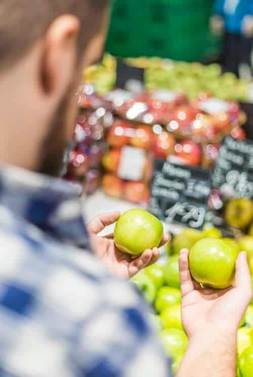 Man holding two apples in grocery isle