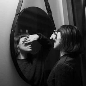 woman in mirror covering eyes