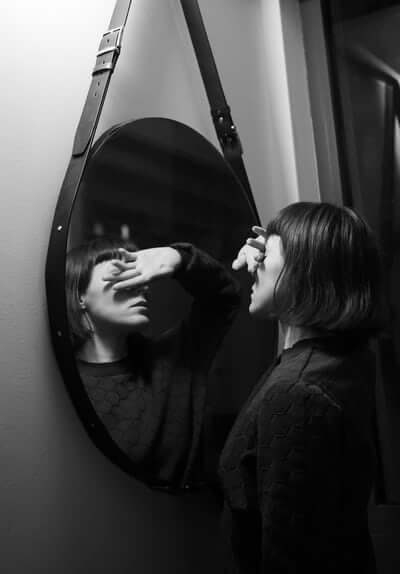 black and white photo of woman covering eyes in mirror
