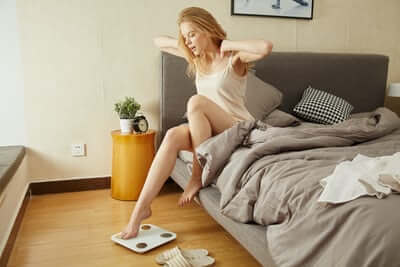 Person Getting Out Of Bed and Checking Weight