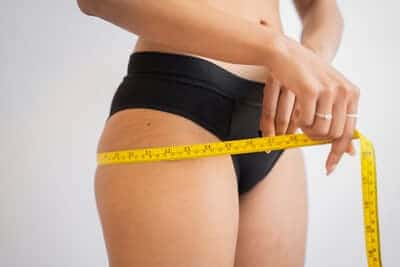 woman in black underwear measuring thighs