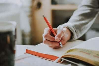 Person writing in journal with red pen