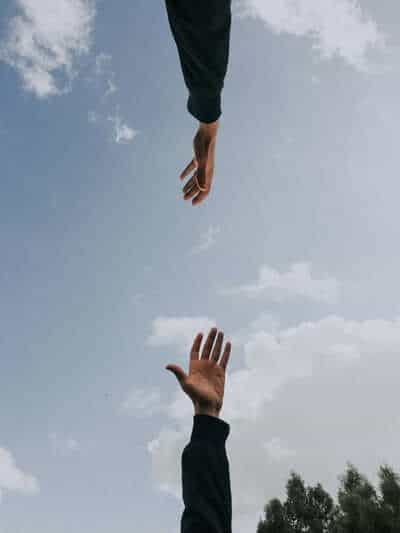 Two hands reaching for each other on blue sky background